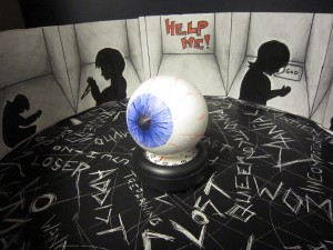 3D eyeball on a table with 2D illustrations around it.