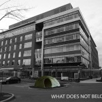 Black and white photo of office building with colour wigwam setup in front of building.