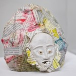A sculpture of a face attached to a ball of newspaper with a pill in its mouth .