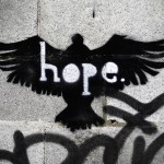 "A spray painting of a bird with the word ""hope"" stencilled out of it."