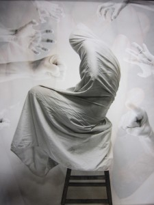 A digital image of a figure wrapped in a white fabric with hand pointing at it in the background