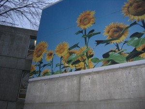 Photograph of a painting of sunflowers with real leaves in front.