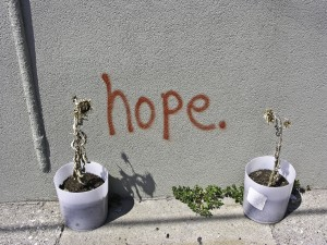 "The word ""hope"" spray painted on a wall between two pots of dying sunflowers."