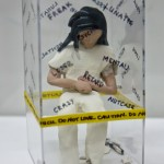 A clay figure in a plexiglass box.