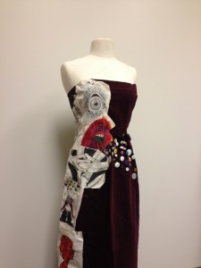 A dress  made of multiple different fabrics and patterns displayed on a manikin.