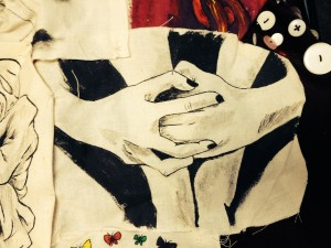 A drawing of two hand holding each other on a piece of fabric