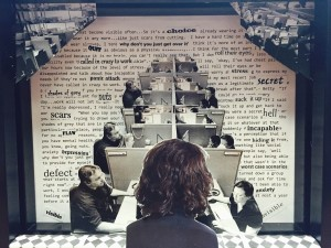 An art peice where there is a repetition of  images where people are sitting at office cubicles  facing each other, with the backside of a single person standing in the foreground and a wall of text in the background