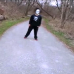 Mysterious masked person standing in a park trail